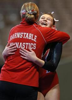 Barnstable's Tali Twomey was all smiles as she got a hug from a coach following her beam performance during the MIAA 2013 State Championship Girl's Gymnastics Meet at the DCU Center in Worcester.