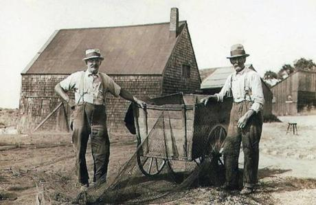 In a scene typical at the time, Captain Elbridge Woodbury and his brother Frank mending and loading nets onto their cart. Elbridge was 71 in 1930 and Frank was 74. A book on Lane's Cove identifies the shack at rear as the one currently under repair