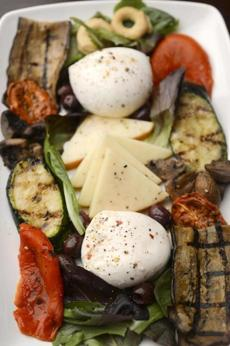 An antipasto platter with a variety of mozzarella and roasted vegetables.