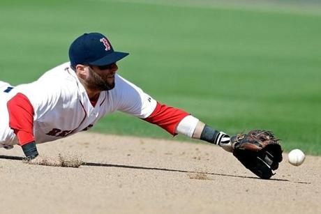 Boston Red Sox's Dustin Pedroia dives for a single hit by New York Yankees' Eduardo Nunez, to score Corban Joseph, in the sixth inning of an exhibition spring training baseball game on Sunday, March 3, 2013, in Fort Myers, Fla. (AP Photo/David Goldman)