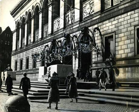 April 18, 1937: This view of the facade of the library shows the library's seal over the doors, flanked by the seals of Massachusetts and Boston. They were the work of Augustus Saint-Gaudens, brother of the sculptor who carved the lions on the grand staircase.