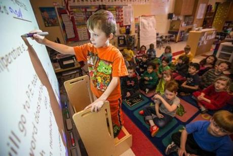 Kindergartner Owen O'Donoghue, 5, uses a SMART board to answer questions at Cunningham Elementary School in Milton.