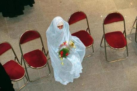 In Iran, a bride waits for her groom at a 2001 wedding.