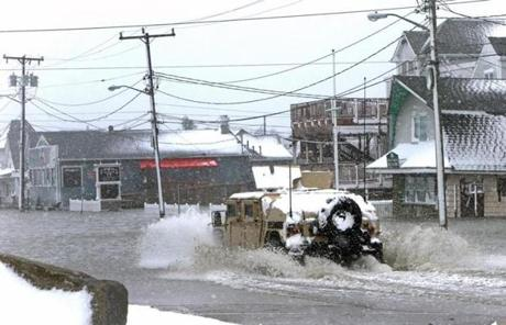A National Guard humvee made its way through the flooded Esplanade section of Brant Rock in Marshfield.