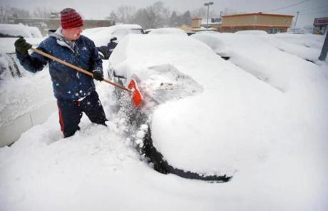 Geoff Fales, a business manager at Lance Buick in Mansfield, cleaned off one of the 250 snow-covered cars in the lot.