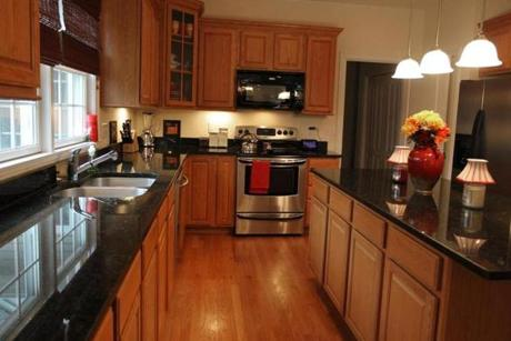 The Kitchen Features Oak Cabinets Dark Granite Counters And Floors