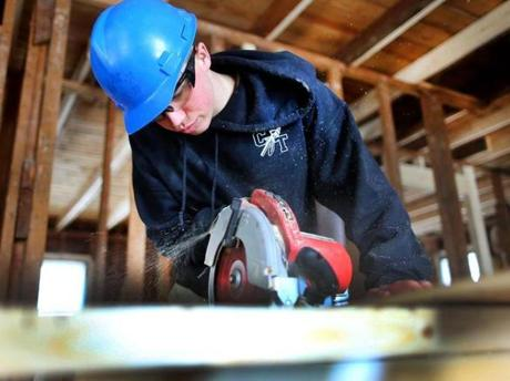 Brendan Dacey, 17, of Dedham cut a piece of plywood for a floor section. Globe staff photo by John Tlumacki