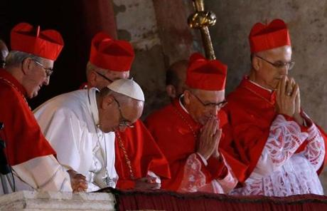 Newly elected Pope Francis bowed in prayer on a balcony at  St. Peter's Basilica.