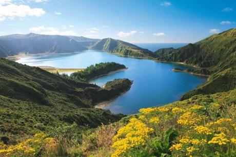 "Lagoa do Fogo, or ""Fire Lake,"" is a gorgeous blue lake sitting in a volcanic crater rimmed by green mountains."