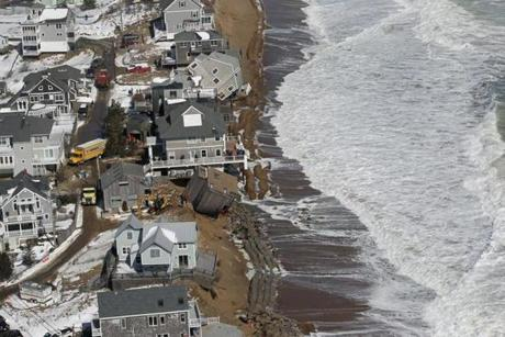 Moving trucks and construction equipment prepared to remove damaged homes as the ocean pounded the coastline on Plum Island on March 9.