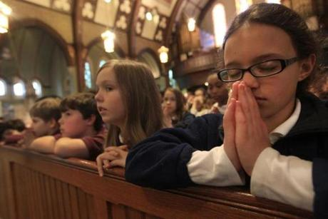 Fourth-grader Sophia Thomas and her class at St. Mary of the Assumption Elementary School prayed for the election of the pope during noontime Mass at St. Mary of the Assumption Church in Brookline.