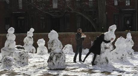 COLD SHOULDER: Posing with snowmen in Titus Sparrow Park in Boston's South End on March 10