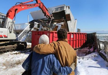 Stephen and Sharon Bresnahan held each other as their fallen Plum Island home, ravaged by the storm, was torn down.