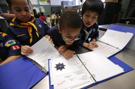 Isiah Pires (left), Kyre Ambrose, and Kerry Nguyen looked over documents together during their pack meeting.