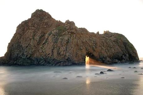 Sun setting through arch in rock at Pfeiffer Beach.