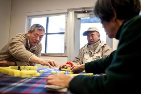 Left to right: Fulu Wang, Dewen Liang, and Feng Liu gather together and play the traditional Chinese game mah-jongg on a Sunday during the Acton Chinese Language school classes.