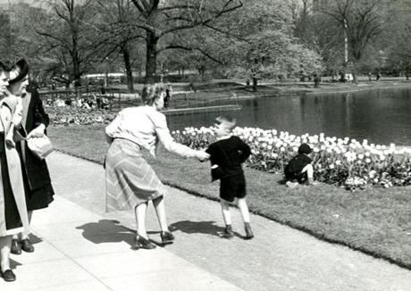 May 23, 1948: Averting a potential flower attack, a mother grabbbed her son's arm before he made a wild dash to join his curious brother (right) who is already down on his knees in the flower bed.