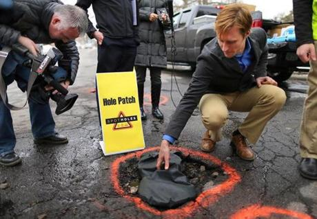 Noah Gostout demonstrated how the Hole Patch sack temporarily fixes potholes, on Bowdoin Avenue on Thursday.