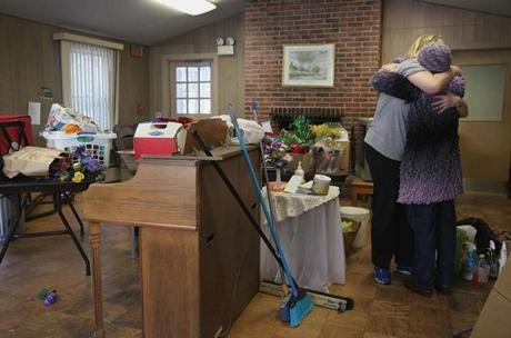 Volunteer Caroline Cheshire embraced Mary Clunan, who helped to disassemble chairs at the Newport Park recreation room in Manchester By The Sea,