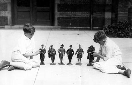 Boys in front of the museum's first location, near Jamaica Pond, line up toy soldiers from the museum's collection in an undated photo.