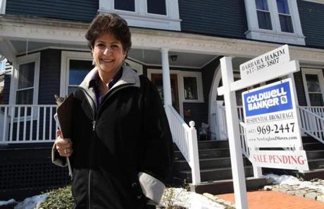 Realtor Barbara Hakim stands in front of a house she sold in Brookline. She's recently seen properties get many offers in a week.