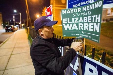 For candidates, Menino's endorsement has become highly coveted because of his favorable image and vast political machine. Volunteer Chuck DiPrima put up campaign signs for Elizabeth Warren and other candidates outside East Boston High School Nov. 5, 2012.