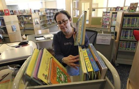 Library assistant Karen Cagan tags books at the new Westwood library.