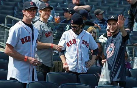 A group of Red Sox fans mingled with a Yankees fan, right, in the stands before the game.