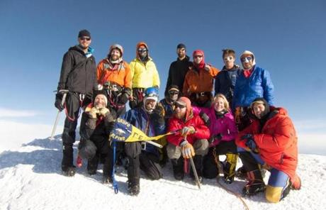 SLIDER Vanessa O'Brien ( pink jacket first row) pictured on the Summit of Denali 20,320 feet on June 19, 2012 with 3 AMS teams including her guide Colby Coombs (kneeling in red jacket far right).