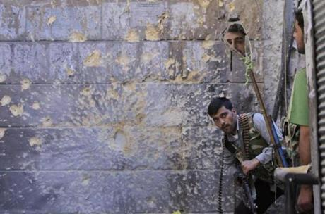 A Free Syrian Army soldier, right, looked through a mirror to see Syrian troops in the old city of Aleppo in September.