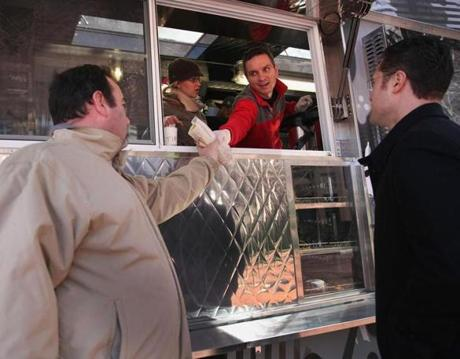 Raul Jurca handed out muffaletta piadini to customers Erik Killough (left) and Jamie McKenna.