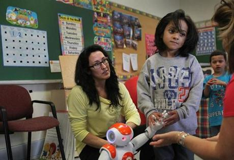 Jadiel Vargas, with teacher Bernadette Roy, held a robot's hand during one display.
