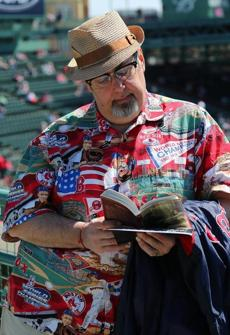 BOSTON, MA. 04/ 08 /13:WEARING HIS OPENING DAY SHIRT Baer Tierkel from Amherst has been coming to opening day for 30 years in a row reads a James Joyce novel pre game. Opening Day for the Red Sox at Fenway Park who played against the Orioles ( David L Ryan/Globe Staff Photo ) SECTION: SPORTS TOPIC Red Sox-Orioles(1)
