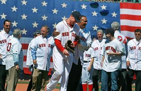 Jim Rice hugged a smiling Jon Lester following the ceremonial first pitches, as former Red Sox players looked on.