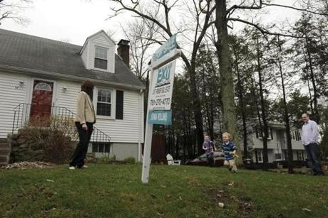 Stacy and Jeff Corbo and her two children Gavin, 5, and Eli, 3 in front of their Burlington home which was at the time under contract after it was on the market for only one day.