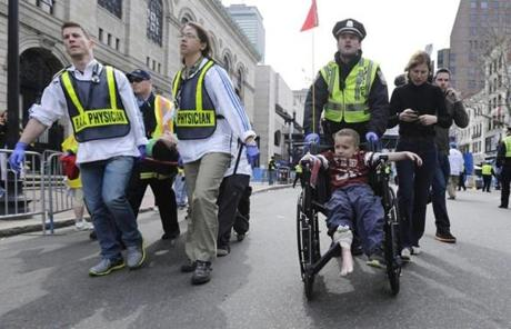 A Boston police officer wheeled an injured boy down Boylston Street as medical workers carried an injured runner.