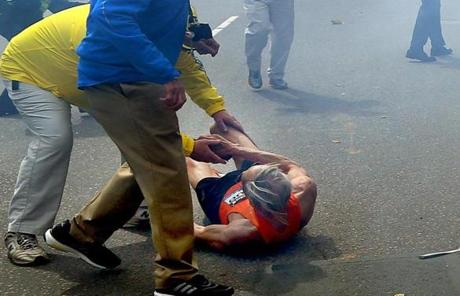A marathon volunteer helped a runner knocked to the ground by the explosions.