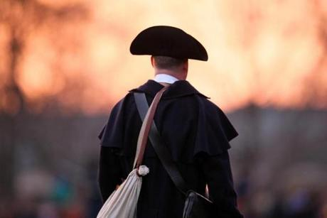 April 15, 2013-LEXINGTON--- PATRIOTS' DAY LEXINGTON, MA -- Minute Man waits on the Battle Green as the sun rises in Lexington as The Battle of Lexington is to begin at the same time it did on April 19th, 1775. globe staff photo: Joanne Rathe The Boston Globe metro )