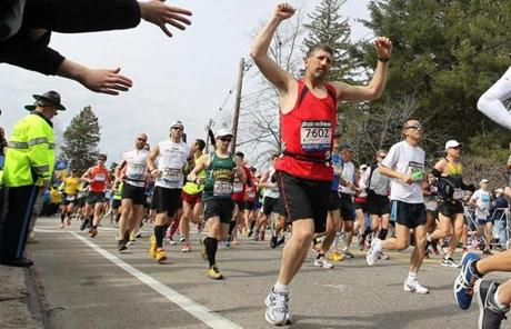 Chris Royer, of Coventry, Vt., raised his hands as he began running the marathon.