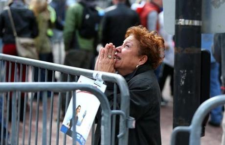 A woman knelt and prayed at the scene of the first explosion at the marathon finish line.