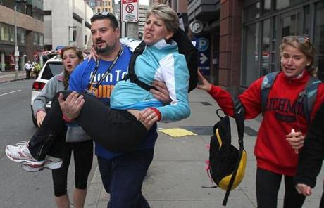 Former New England Patriots lineman Joe Andruzzi carried a woman on Exeter Street after the explosions.