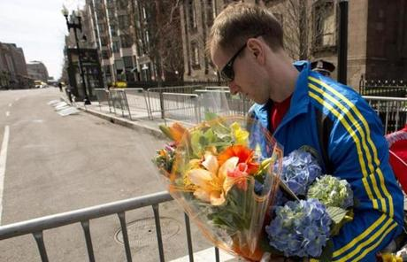 A man in a Boston Marathon 2013 shirt carried flowers.