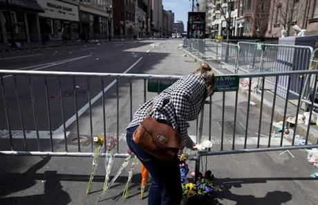 A woman placed flowers at the intersection of Boylston and Arlington streets Tuesday.