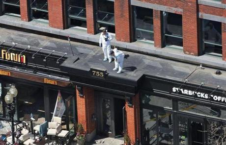 Two people stood above 755 Boylston St.