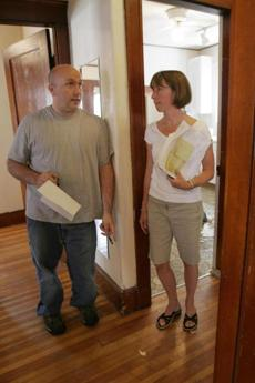 Elizabeth Davis-Edwards is shown in 2005 discussing repairs with friend Steve Allen in a Medford home she was flipping; she now says she'd never attempt it again.