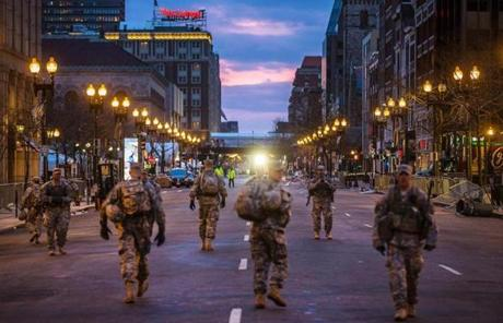 Members of the military walked along Boylston Street near the finish line of the Boston Marathon.