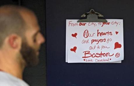 A sign expressing condolences for the attacks hung in the Red Sox dugout as Dustin Pedroia passed it.