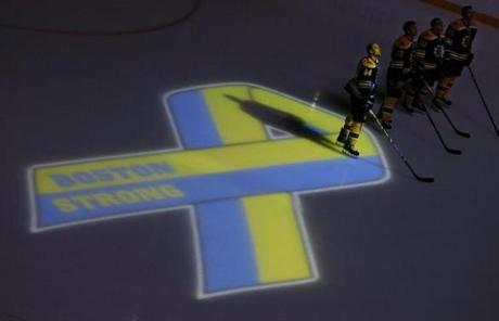 Bruins defenseman Dennis Seidenberg (left), stood next to a ribbon projected onto the ice.