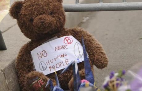 A teddy bear at the barricade memorial with a note saying