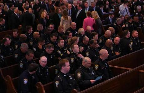 Boston Police Department officers in  pews at the Cathedral of the Holy Cross before the memorial service.